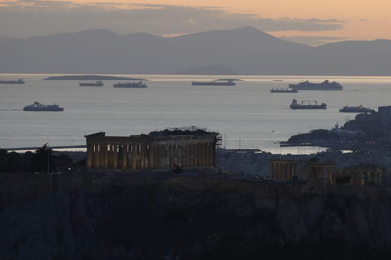 The Parthenon temple is illuminated atop of the Acropolis hill as a ferry approaches the port of Piraeus as another one departs in Athens, Monday, Oct. 26, 2020. (AP Photo/Thanassis Stavrakis)