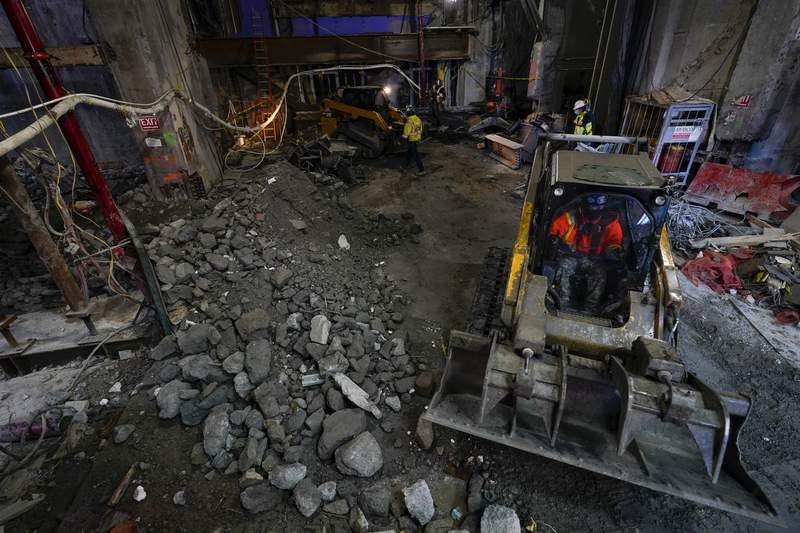 Construction workers clear out debris from the demolition of the original building at TSX Broadway under construction, Thursday, Oct. 29, 2020, in New York's, Times Square. The 46-story mixed-use property will house 75,000 square feet of retail space, a a 4,000-square-foot performance venue including an outdoor stage, an outdoor food and beverage terrace and a luxury hotel. U.S. construction spending rose 0.3% in September, the fourth straight monthly gain after a coronavirus-caused spring swoon. (AP Photo/Mary Altaffer)