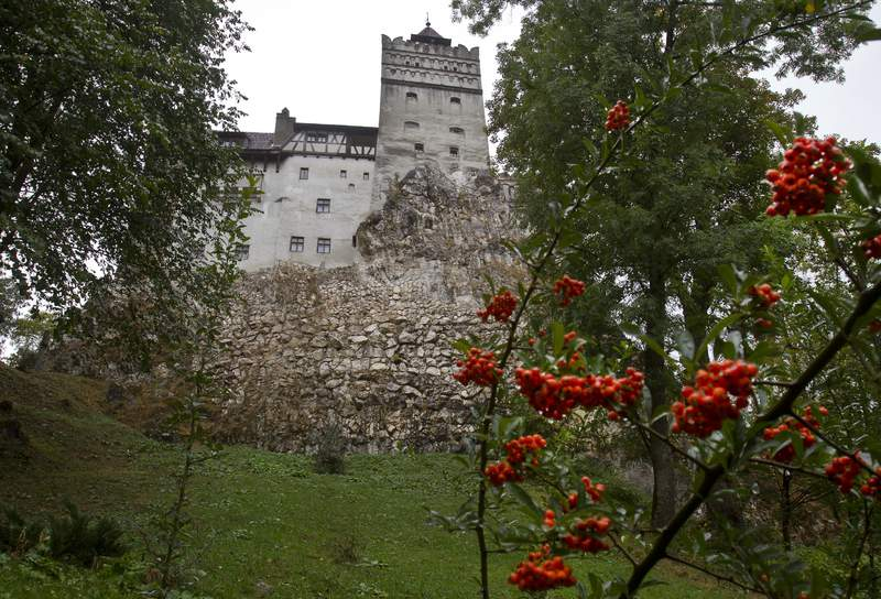 FILE - In this Saturday, Oct. 8, 2011 file picture, the Gothic Bran Castle, better known as Dracula Castle, is seen on a rainy day in Bran, in Romania's central Transylvania region. Romanian authorities have set up a COVID-19 vaccination center in a medieval building in Bran, not far from the castle, as a means to encourage people to vaccinate and also to boost tourism which has decreased in the area as a result of the pandemic. (AP Photo/Vadim Ghirda, File)