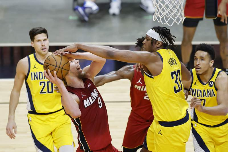 Myles Turner of the Indiana Pacers blocks a shot by Kelly Olynyk of the Miami Heat during the third quarter at American Airlines Arena on March 19, 2021 in Miami, Florida.