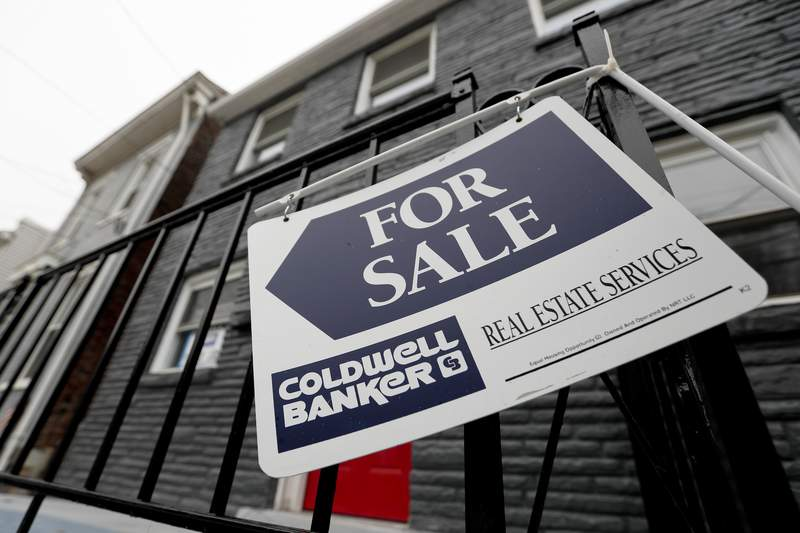 FILE- In this Jan. 4, 2019, file photo a sign hangs outside a house for sale in Pittsburgh's Lawrenceville neighborhood.  On Thursday, May 21, 2020, Long-term U.S. mortgage rates eased this week in a housing market battered by the shutdown spurred by the coronavirus pandemic. Rates hovered near all-time lows as the benchmark 30-year home loan stayed below 3.30% for the fourth straight week.(AP Photo/Keith Srakocic, File)