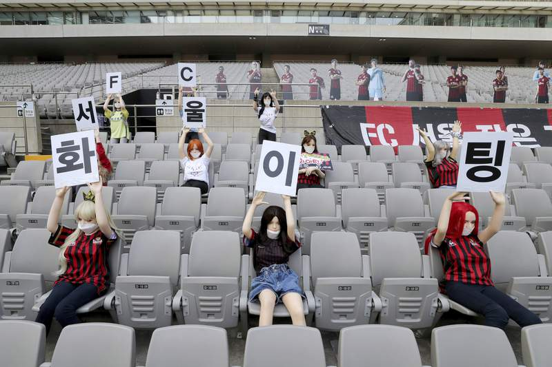 """In this May 17, 2020 photo, Cheering mannequins are installed at the empty spectators' seats before the start of soccer match between FC Seoul and Gwangju FC at the Seoul World Cup Stadium in Seoul, South Korea. A South Korean professional soccer club has apologized after being accused of putting sex dolls in empty stands during a match Sunday in Seoul. In a statement, FC Seoul expressed """"sincere remorse"""" over the controversy, but insisted that it used mannequins, not sex dolls, to mimic a home crowd during its 1-0 win over Gwangju FC at the Seoul World Cup stadium. The signs read """" Go! FC Seoul."""" (Ryu Young-suk/Yonhap via AP)"""
