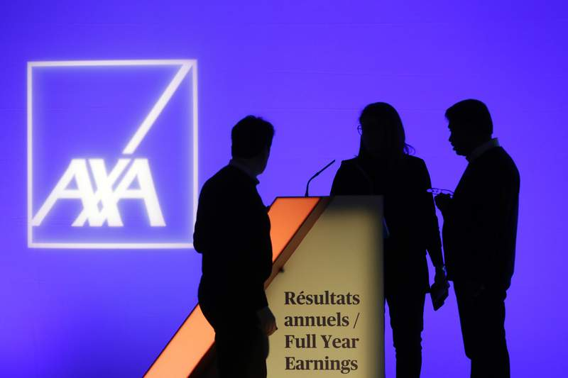 FILE - In this Thursday, Feb. 21, 2019, file photo, people stand in front of the logo of AXA Group prior to the company's 2018 annual results presentation, in Paris. Cybercriminals have hit four Asian subsidiaries of the Paris-based insurance company AXA with a ransomware attack, impacting operations in Thailand, Malaysia, Hong Kong and the Philippines, the insurer said. (AP Photo/Thibault Camus, File)