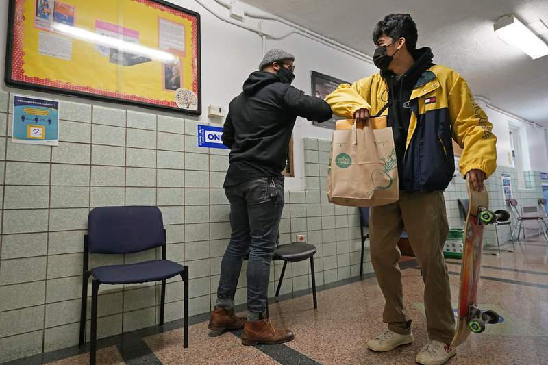 West Brooklyn Community High School principal Malik Lewis, left, bumps elbows with former student Jason Cardoso after Cardoso came to pick up the diploma he earned when he graduated in March, Thursday, Nov. 19, 2020, in the Brooklyn borough of New York. Cardoso, along with many West Brooklyn students who graduated in the spring, was unable to get back to the school because he's working during school hours. The school has been forced to close three times since spring due to coronavirus. (AP Photo/Kathy Willens)