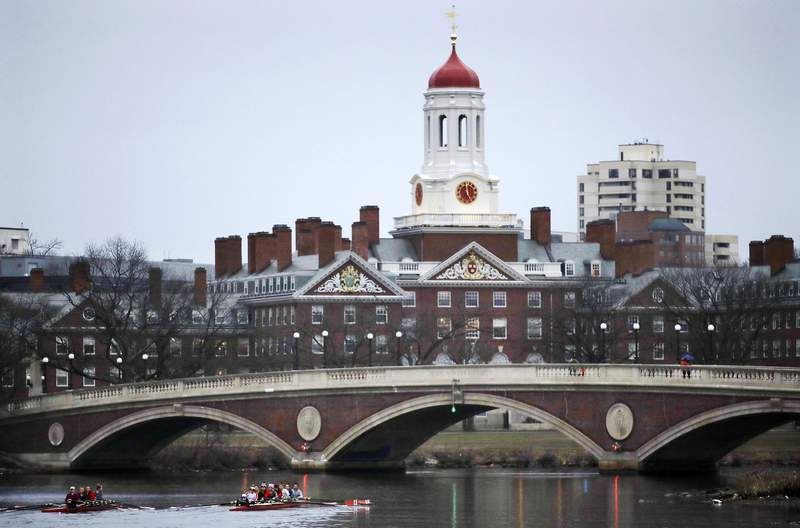 FILE - In this March 7, 2017, file photo, rowers paddle along the Charles River past the Harvard University campus in Cambridge, Mass.  (AP Photo/Charles Krupa, File)