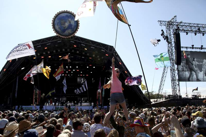 FILE - In this Sunday, June 30, 2019 file photo, revelers react to Kylie Minogue as she performs at the Glastonbury Festival, Somerset, England. Organizers of live events in the U.K., such as festivals and theaters, have given their partial support to a new coronavirus-related insurance initiative aimed at easing their financial worries. In a statement late Thursday, Aug. 5, 2021 the government said it was backing a 750 million-pound ($1 billion) insurance scheme that will cover the cancellation costs incurred by the hard-hit live events sector in the event of further lockdowns in the year from Sept. (Photo by Grant Pollard/Invision/AP, File)