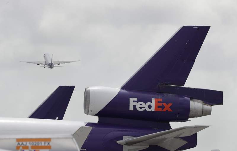 A FedEx aircraft takes off past the tail of another parked on the tarmac of Miami International Airport, Monday, July 27, 2020, in Miami. FedEx plans to cut up to 6,300 jobs in Europe after its acquisition of TNT Express. FedEx said Tuesday, Jan. 19, 2021,  that the cuts will take place over 18 months and include express-delivery operations and back-office employees of TNT across the continent.  (AP Photo/Wilfredo Lee)
