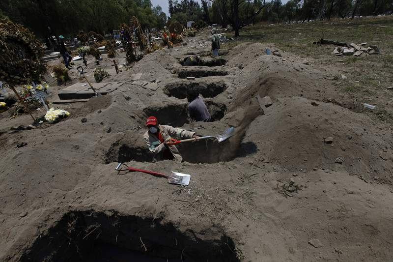 """Melvin Sanaurio, front, digs a grave at the San Lorenzo Tezonco Iztapalapa cemetery in Mexico City, Tuesday, June 2, 2020, amid the new coronavirus pandemic. """"It takes me more than an hour to dig one grave,"""" Sanaurio said. (AP Photo/Marco Ugarte)"""