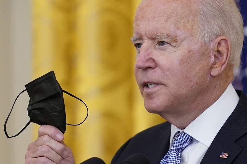 El presidente Joe Biden sostiene una mascarilla mientras habla sobre unas medidas nuevas relacionadas con el coronavirus para los trabajadores federales en la Casa Blanca, en Washington, el jueves 29 de julio de 2021. (AP Foto/Susan Walsh)