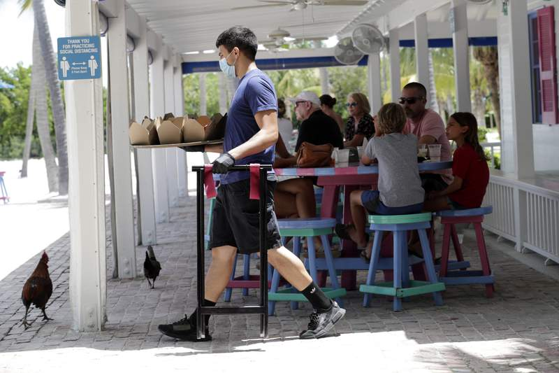 FILE - In this June 1, 2020 file photo, Charles Perez wears a protective face mask and gloves as he waits on tables at the Morada Bay Beach Cafe in Islamorada, in the Florida Keys, during the new coronavirus pandemic.  Repealing statewide mask mandates and criticizing the Biden administrations unemployment-based formula for distributing billions in federal aid has put Republican governors and their approach to handling the coronavirus pandemic back in the spotlight.  (AP Photo/Lynne Sladky)