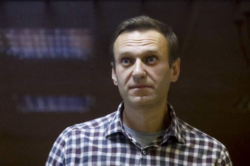 """FILE - In this Saturday, Feb. 20, 2021 file photo, Russian opposition leader Alexei Navalny stands in a cage in the Babuskinsky District Court in Moscow, Russia. Imprisoned Russian opposition leader Alexei Navalny, who has been on hunger strike since March 31, described threats to force-feed him, using """"straitjacket and other pleasures,"""" in a message from behind bars Friday, April 16. In an Instagram post, Navalny said an official told him that a blood test indicated his health was deteriorating and threatened to force-feed him if he continues to refuse to eat. (AP Photo/Alexander Zemlianichenko, File)"""