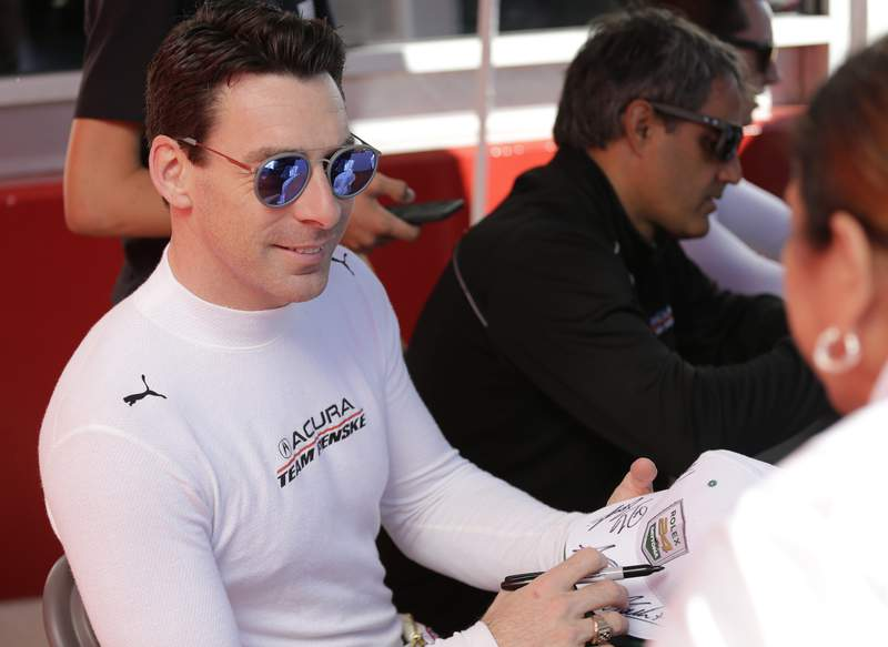 FILE - In this Jan. 25, 2020, file photo, Acura Team Penske driver Simon Pagenaud, left, signs autographs before the Rolex 24-hour auto race at Daytona International Speedway in Daytona Beach, Fla. Pagenaud won IndyCar's first iRace on an oval as he used strategy to win at virtual Michigan International Speedway. (AP Photo/Terry Renna, File)