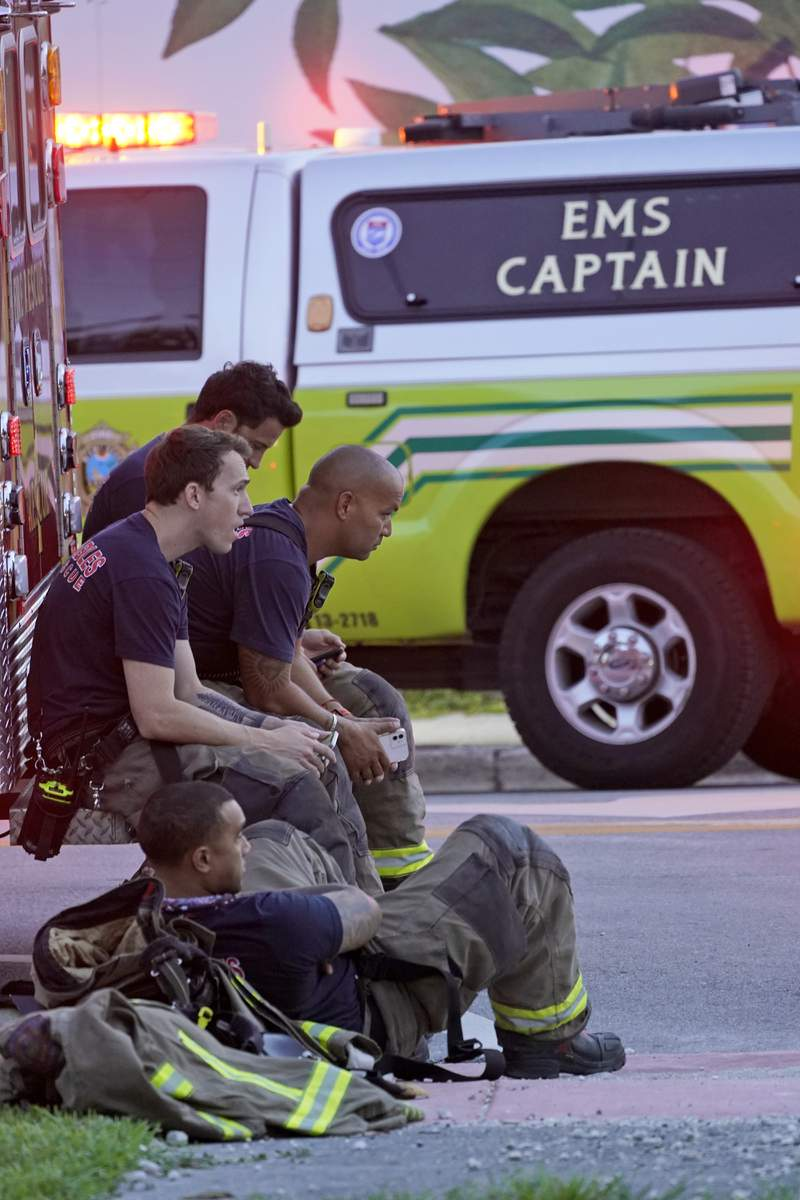 Firefighters wait near the site of a partial building collapse, Thursday, June 24, 2021, in Surfside, Fla. (AP Photo/Wilfredo Lee)