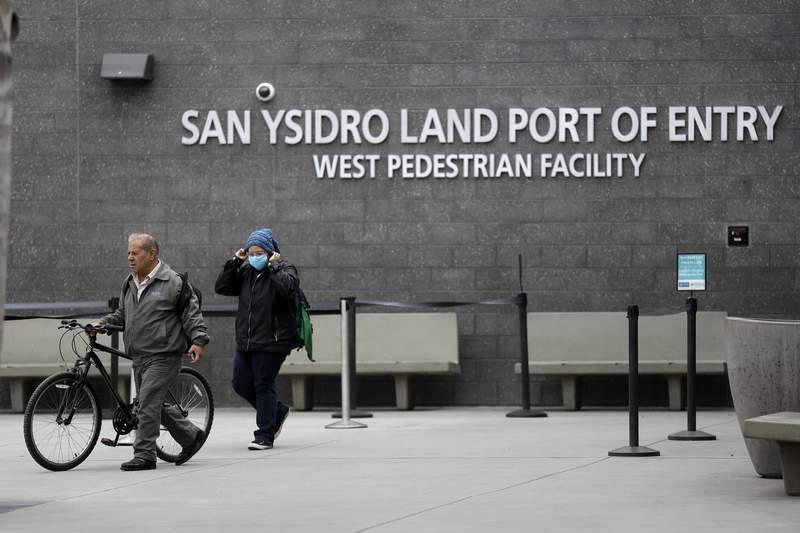 ARCHIVO - En imagen de archivo del 20 de marzo de 2020, una mujer se ajusta su sombrero y la mascarilla a su llegada a Estados Unidos procedente de Tijuana, Mxico, cruzando a pie por la garita de San Ysidro en San Diego. (AP Foto/Gregory Bull, archivo)
