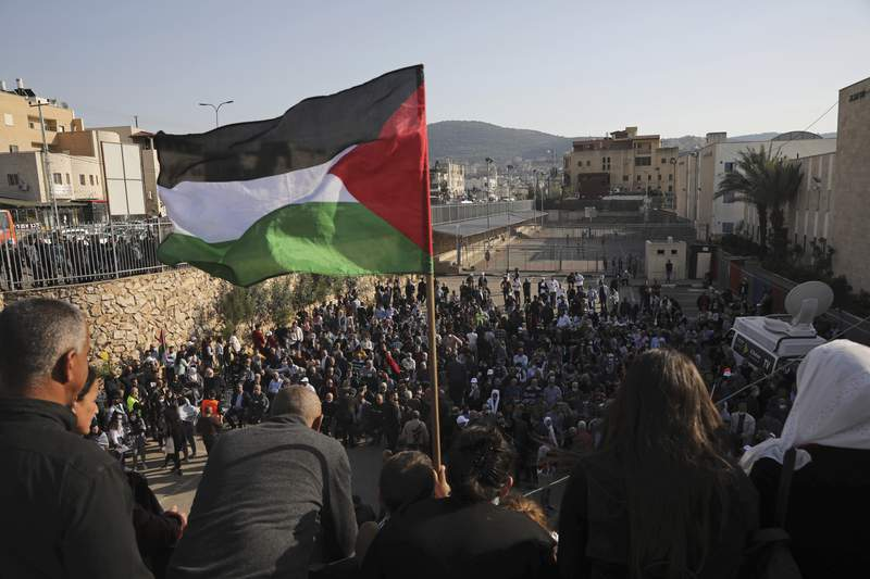 A Palestinian flag flies over the annual Land Day rally in the Arab city of Arraba, northern Israel, Tuesday, March 30, 2021. Land Day rallies by Palestinians protest what they say are discriminatory policies and to commemorate the deaths of six Arab protesters who were killed by police on March 30, 1976, while demonstrating against an Israeli plan to confiscate Arab land. (AP Photo/Mahmoud Illean)