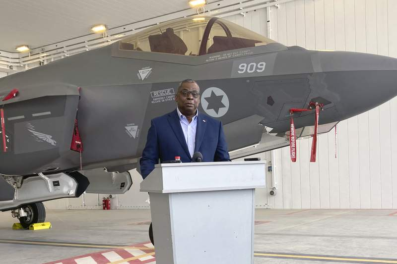 U.S. Defense Secretary Lloyd Austin speaks to reporters at Israel's Nevatim air base Monday, with an Israeli F-35 fighter jet in the background, at Nevatim Israeli Air Force Base, Monday, April 12, 2021 in Israel. (AP Photo/Robert Burns)