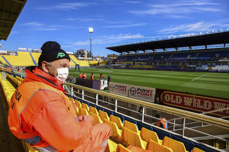A man wears a mask as he sits in the stands ahead of a Serie A soccer match between Parma and Spal was scheduled to be played, in Parma, northern Italy, Sunday, March 8, 2020. Parma and Spal players were ready to enter the field at Ennio Tardini stadium in Parma when they received the news that Italys sports minister Vincenzo Spadafora said that the countrys football federation should consider suspending the games. (Piero Cruciatti/LaPresse via AP)