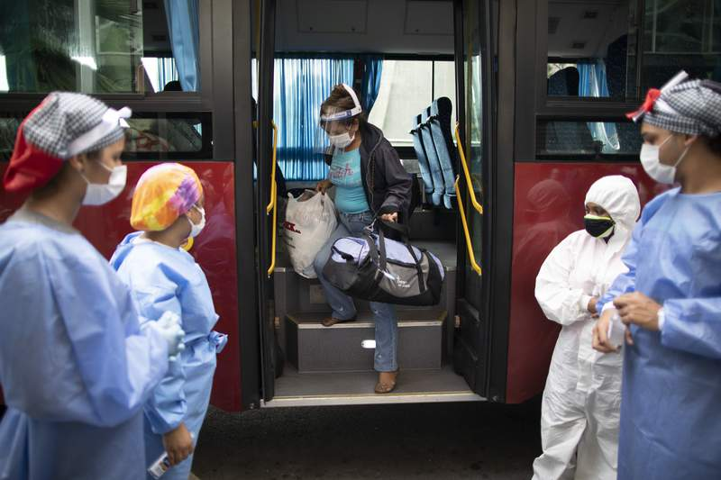 A woman who tested positive for COVID-19 arrives on a government bus to a former students residence being used to quarantine asymptomatic patients infected with the new coronavirus in Caracas, Venezuela, Tuesday, Aug 25, 2020. (AP Photo/Ariana Cubillos)