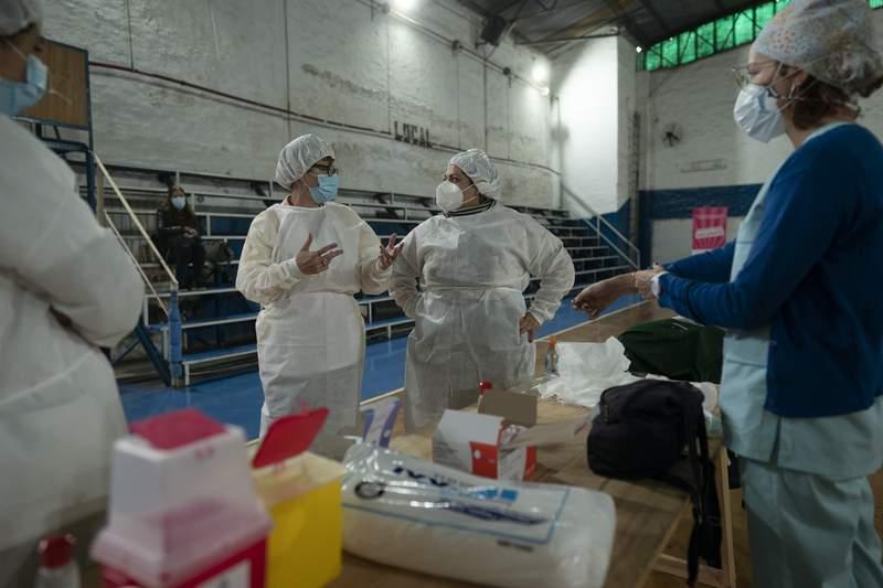 La supervisora de enfermera Paola Almirn, centro derecha, organiza una campaa de vacunacin contra el COVID-19 en un gimnasio en las afueras de Buenos Aires, Argentina, el viernes 9 de julio de 2021.  (AP Foto/Vctor R. Caivano)