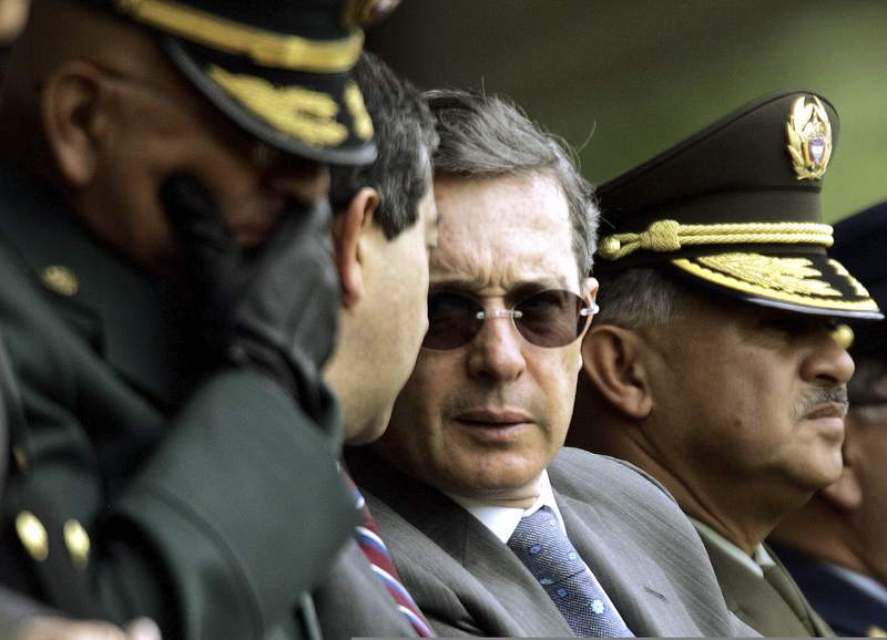 FILE - In this June 9, 2006 file photo, Colombia's President Alvaro Uribe, center, speaks with Defense Minister Camilo Ospina, second left, during a police ceremony in Bogota, Colombia. The U.S. Department of Defense suspected back then that the now former president harbored ties with violent paramilitaries but likened it to a necessary evil in the fight against leftist rebels, according to a newly declassified memo from his early years in office. (AP Photo/Fernando Vergara, File)
