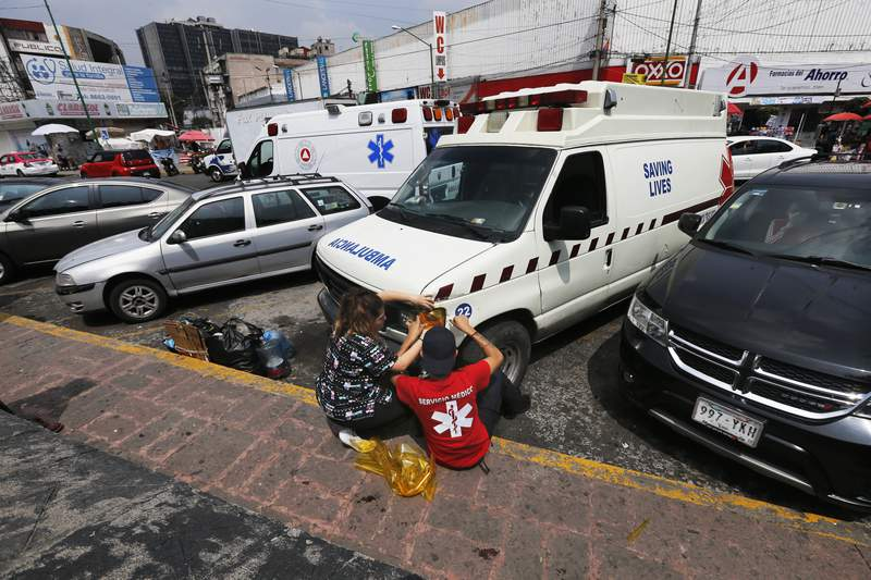 """People repair a """"pirate"""" ambulance light outside the General Hospital in Mexico City, Saturday, Sept. 12, 2020. The poorly equipped, often broken-down rattletraps ply Mexico City streets listening to emergency radio dispatch frequencies and race to beat legitimate ambulance services to medical emergencies. (AP Photo/Marco Ugarte)"""