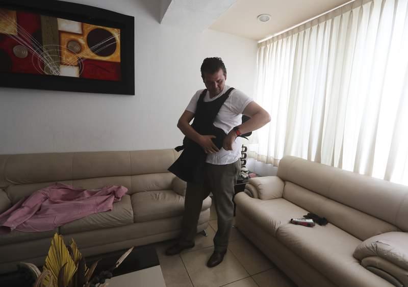 El candidato a la alcalda Guillermo Valencia del Partido Revolucionario Institucional, PRI, se pone su chaleco antibalas en la casa de un familiar antes de hacer campaa en Morelia, estado de Michoacn, Mxico, el viernes 21 de mayo de 2021.  (AP Foto/Marco Ugarte)