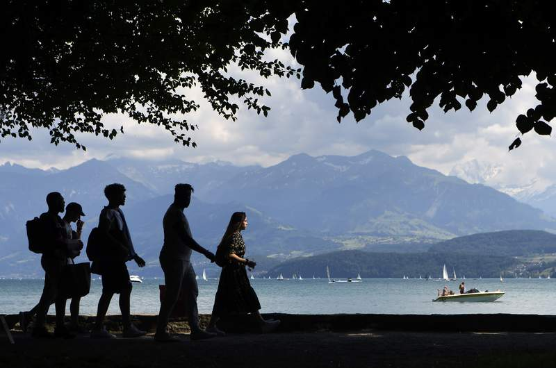 People enjoy the sun on the shores of Lake Thun, in Thun, Switzerland, Monday June 1, 2020.  The sunny and warm weather, Monday, has attracted visitors to rest and enjoy water sports. (Anthony Anex/Keystone via AP)
