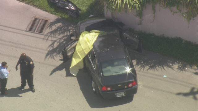 A view from Sky 10 shows a yellow tarp covering the front driver's seat of a car where a man was found shot to death in Opa-locka.