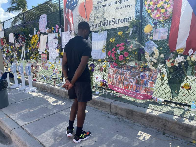 Miami Heat legend Dwyane Wade visits the memorial wall set up for Surfside condo collapse victims.