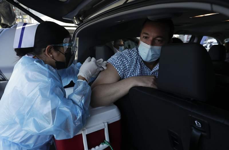 Un hombre recibe la vacuna de AstraZeneca contra el COVID-19 el jueves 22 de abril de 2021 en el estacionamiento del estadio Rommel Fernndez, en Ciudad de Panam. (AP Foto/Arnulfo Franco)