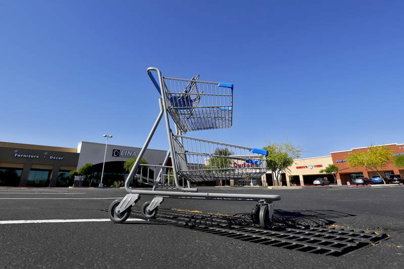 A lone shopping cart sits in an empty parking lot Friday, April 24, 2020, outside closed businesses in Phoenix. The outbreak of the coronavirus has dealt a shock to the global economy with unprecedented speed and retail stores may have been changed forever by the outbreak. (AP Photo/Matt York)