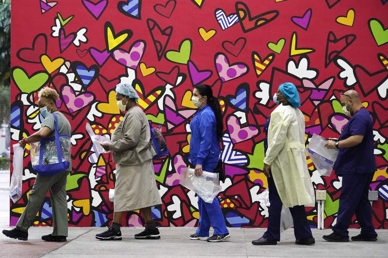 Healthcare workers line up for free personal protective equipment in front of a mural by artist Romero Britto at Jackson Memorial Hospital last month in Miami.