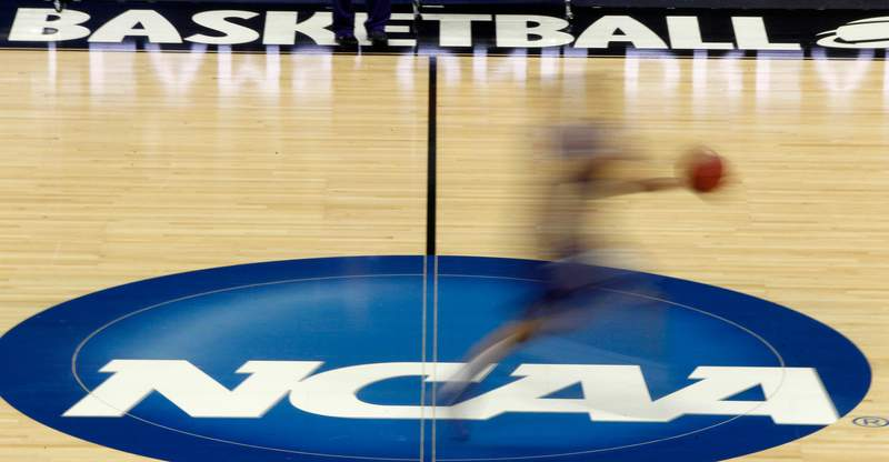 FILE - In this March 14, 2012, file photo, a player runs across the NCAA logo during practice in Pittsburgh before an NCAA tournament college basketball game. A court decision the NCAA says will hurt college sports by allowing student-athletes to be paid vast sums of money will go into effect. That's after the Supreme Court declined Tuesday to intervene at this point. Justice Elena Kagan denied the NCAAs request to put a lower court ruling on hold at least temporarily while the NCAA asks the Supreme Court to take up the case.  (AP Photo/Keith Srakocic, File)