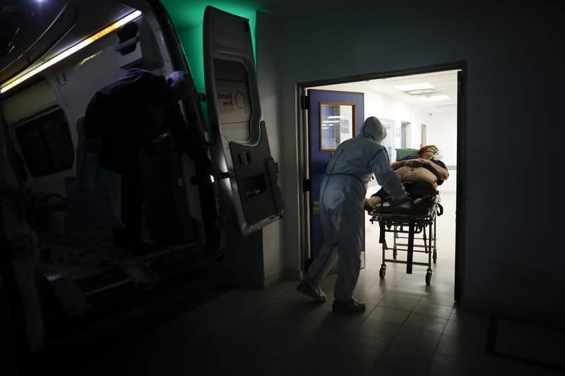 ARCHIVO - En esta fotografa de archivo del 1 de mayo de 2021 un trabajador de la salud traslada a una mujer sospechosa de tener COVID-19 en el Hospital Dr. Norberto Ral Piacentini en Lomas de Zamora, Argentina. El presidente Alberto Fernndez anunci el 21 de mayo un estricto confinamiento por primera vez este ao luego de un rebrote de casos y muertes por COVID-19. (AP Foto/Natacha Pisarenko, Archivo)