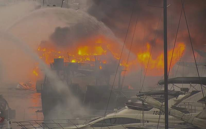 In this image made from video provided by TVB, fire service boat spray water at boats at Aberdeen South Typhoon Shelter in Hong Kong Sunday, June 27, 2021. A fire engulfed 16 vessels in a Hong Kong typhoon shelter early Sunday, resulting in at least 10 boats sinking and one person sent to hospital. (TVB via AP)