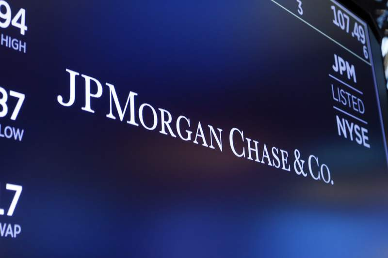 FILE - In this Aug. 16, 2019 file photo, the logo for JPMorgan Chase & Co. appears above a trading post on the floor of the New York Stock Exchange.  JPMorgan Chase & Co. will no longer do business with coal companies and will restrict financing to companies that drill in the Arctic, the company announced Tuesday, Feb. 25, 2020 The announcement came in tandem with the bank announcing it would extend $200 billion in financing to clean and renewable energy companies by 2025.  (AP Photo/Richard Drew, File)