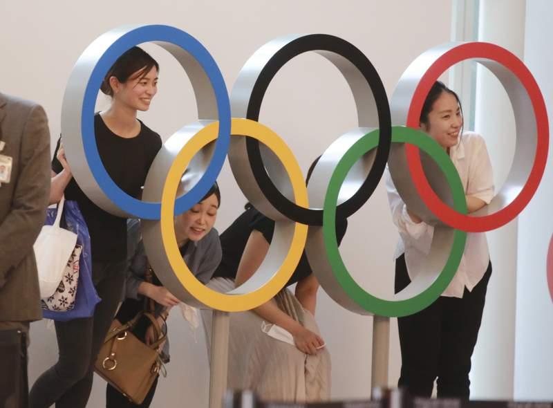 People pose for photo with the Olympics Rings display at Haneda International Airport in Tokyo, Thursday, July 8, 2021. (AP Photo/Koji Sasahara)
