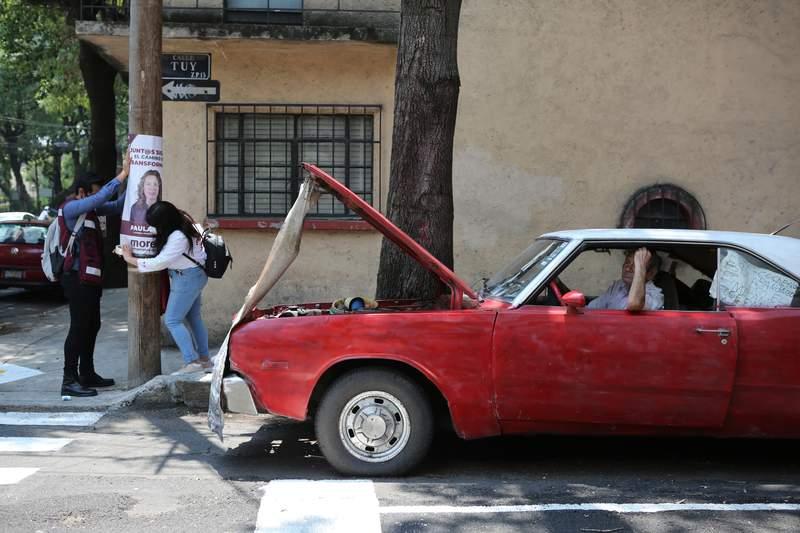 Simpatizantes de la candidata a la alcalda del partido gobernante Morena, Paula Soto, colocan un cartel en un poste elctrico en el ltimo da de campaa previo a las elecciones intermedias del 6 de junio, en la Ciudad de Mxico, el sbado 29 de mayo de 2021. (AP Foto/Ginnette Riquelme)