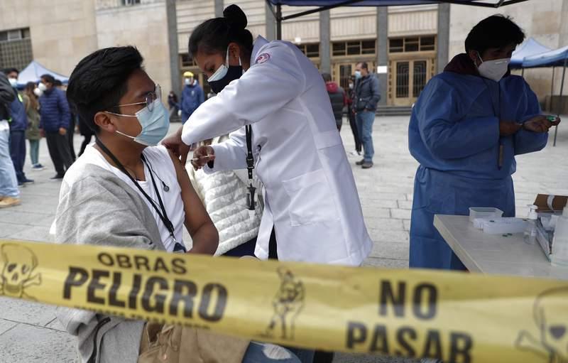 Una estudiante que ayuda a los trabajadores de la salud con las vacunas COVID-19 recibe una inyeccin de la vacuna AstraZeneca en la universidad pblica Universidad Mayor de San Andrs en La Paz, Bolivia, el viernes 9 de abril de 2021. La Organizacin de Estados Americanos y la Organizacin Panamericana de la Salud denunciaron el mircoles la crtica situacin que atraviesan los pases de Latinoamrica por la desigualdad en el acceso a las vacunas contra el COVID-19. (Foto AP/Juan Karita)