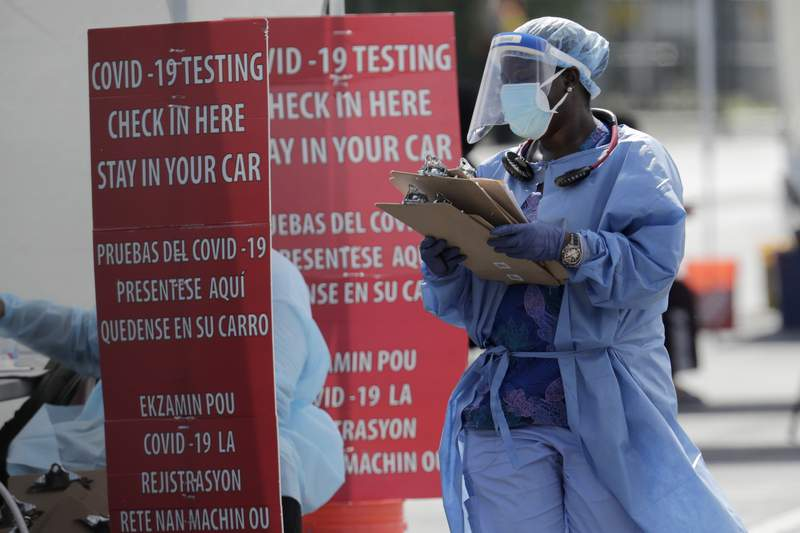 A healthcare worker carries a stack of clipboards at a COVID-19 testing site at the Martin Luther King Jr. Clinica Campesina Health Center Monday in Homestead, Fla.
