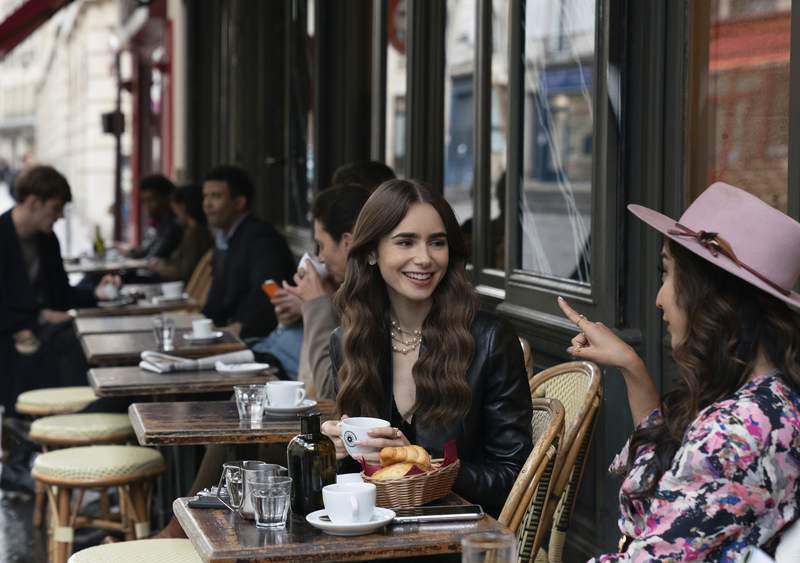 """This image released by Netflix shows Lily Collins, center, in a scene from """"Emily in Paris,"""" premiering on Friday, Oct. 2. (Stephanie Branchu/Netflix via AP)"""