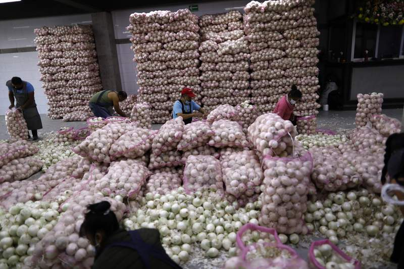 FILE - In this Dec. 8, 2020 file photo, workers, some wearing face masks, bag onions inside the Central de Abastos, the capital's main market, in Mexico City, amid the new cornavirus pandemic.  Mexicos pandemic-hit economy shrank 8.5% in 2020, the largest single-year drop since 1932 and the second consecutive year of economic contraction, according to preliminary data released Friday, Jan. 29, 2021, by the National Statistics and Geography Institute. (AP Photo/Rebecca Blackwell, File)