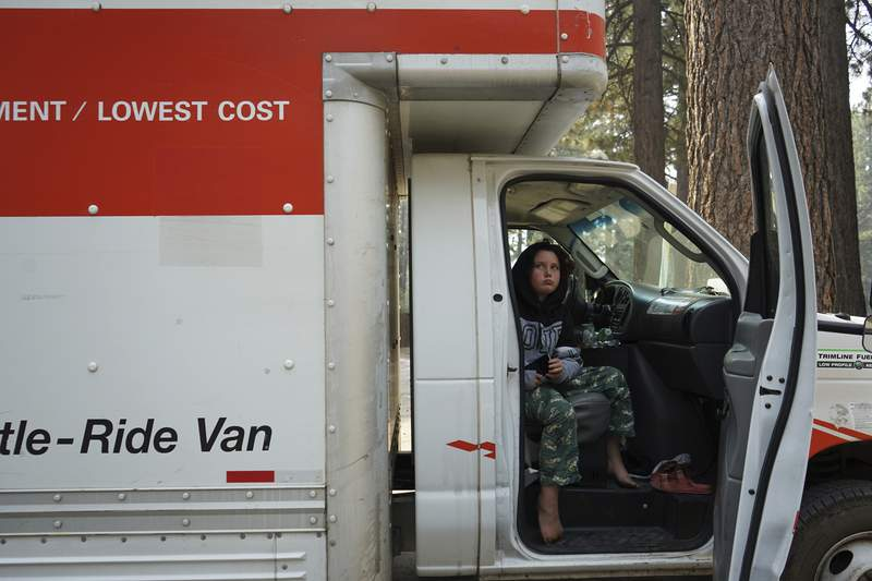 Lela Hill sits in her family's moving truck after returning to South Lake Tahoe, Calif., on Monday, Sept. 6, 2021. Mid-move, her family was among thousands of people who were evacuated from the resort town due to the Caldor Fire last week. (AP Photo/Samuel Metz)