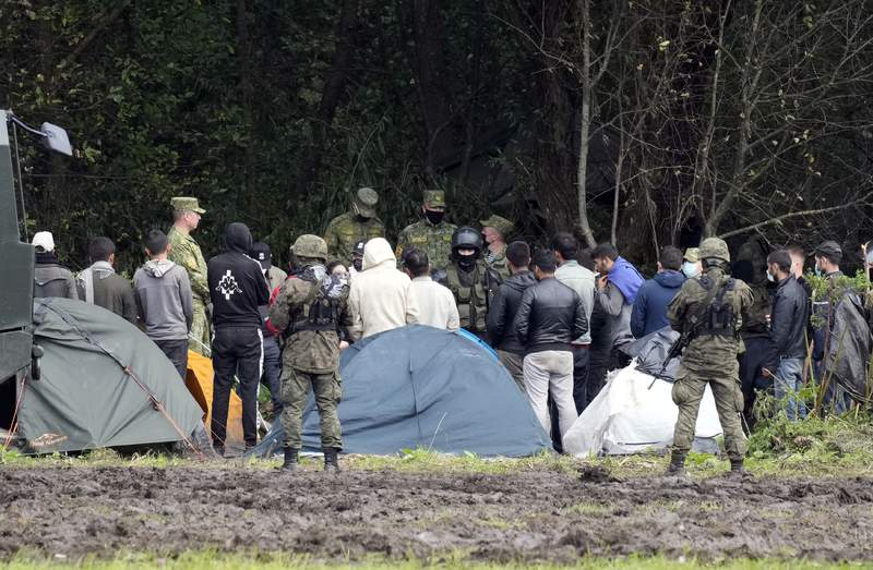 """Polish security forces surround migrants stuck along with border with Belarus in Usnarz Gorny, Poland, on Wednesday, Sept. 1, 2021. Poland has been reinforcing its border with Belarus  also part of the EU's eastern border  after thousands of migrants from Iraq, Afghanistan and elsewhere tried to illegally enter the country. The Polish government says it is the target of a """"hybrid war"""" waged by authoritarian Belarus. Human rights activists are concerned about a group caught along the border, trapped between armed guards on each side. (AP Photo/Czarek Sokolowski)"""