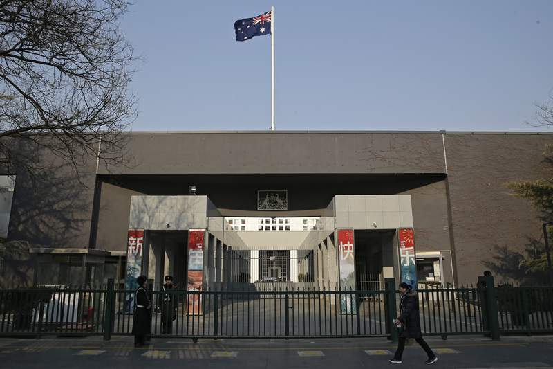 FILE - In this Jan. 24, 2019, file photo, a woman walks by the Australian Embassy in Beijing. China on Thursday, May 6, 2021 suspended an economic dialogue with Australia, stepping up a pressure campaign that began over Australian support for a probe into the origins of the coronavirus. (AP Photo/Andy Wong)