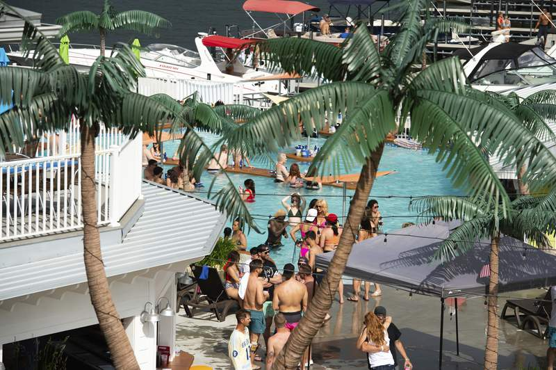 Crowds of people gather at Coconuts Caribbean Beach Bar & Grill in Gravois Mills, Missouri, Sunday, May 24, 2020. Several beach bars along Lake of the Ozarks were packed with party-goers during the Memorial Day weekend. Several political leaders in the St. Louis and Kansas City areas, as well as the state of Kansas' health secretary, have condemned Lake of the Ozarks revelers for failing to practice social distancing, amid fears they could return to areas hard hit by the coronavirus and spread the disease. (Shelly Yang/Kansas City Star via AP)