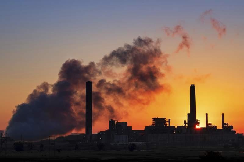 En esta imagen de archivo, tomada el 27 de julio de 2018, la silueta de la planta de energa trmica Dave Johnson se recorta contra el cielo al amanecer, en Glenrock, Wyoming. (AP Foto/J. David Ake, archivo)