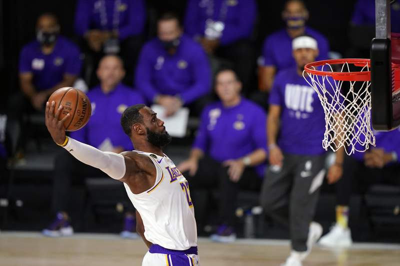 FILE - In this Oct. 11, 2020, file photo, Los Angeles Lakers' LeBron James dunks during the first half in Game 6 of basketball's NBA Finals against the Miami Heat in Lake Buena Vista, Fla. After James emerged from the longest season in NBA history with a fourth ring, he returned home and planned the first Christmas family vacation of his adult life. That's when James learned that his 17th NBA offseason would be unprecedentedly short. (AP Photo/Mark J. Terrill, File)