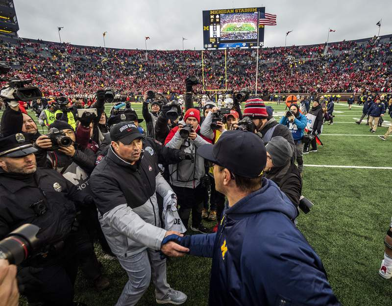 FILE - In this Nov. 30, 2019, file photo, Ohio State head coach Ryan Day, front left, shakes hands with Michigan head coach Jim Harbaugh, front right, after an NCAA college football game in Ann Arbor, Mich. The Big Ten's third football schedule of the 2020 season is highlighted by Michigan-Ohio State on Dec. 12, the final day of the conference's regular-season and the latest date the rivals have ever played. (AP Photo/Tony Ding, File)