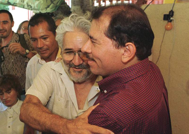 FILE - In this Sept. 21, 1998 file photo, former Sandinista guerrilla leader Eden Pastora embraces former Nicaraguan President and Sandinista National Liberation Front leader Daniel Ortega, in Managua, Nicaragua. Pastora, one of the most mercurial, charismatic figures of Central Americas revolutionary upheavals, has died. His son Alvaro Pastora said Tuesday, June 16, 2020, that he died at Managuas Military Hospital of respiratory failure. (AP Photo/Anita Baca, File)